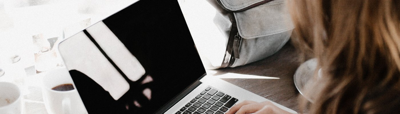 Woman working on laptop in a cafe - Online marketing tips