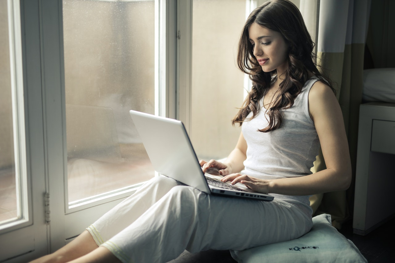 a woman sitting on the floor and working on her laptop
