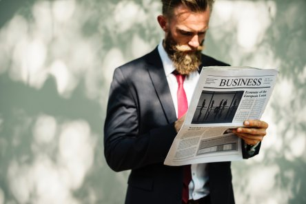 Amazsites.com - a man is reading business newspaper